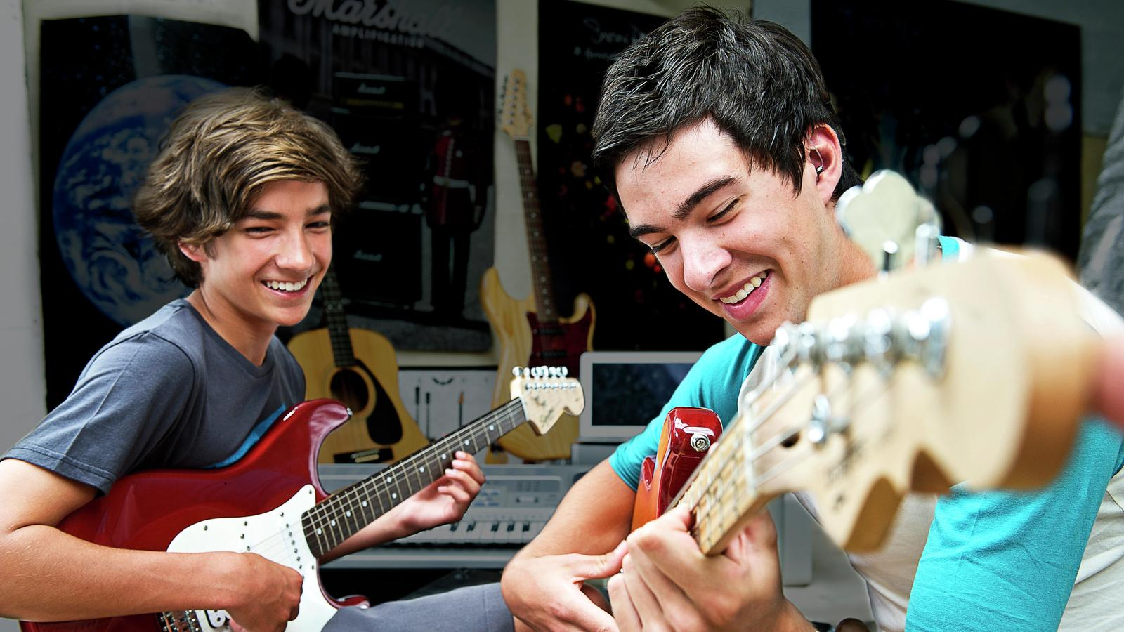 Two teenage males play electric guitar together